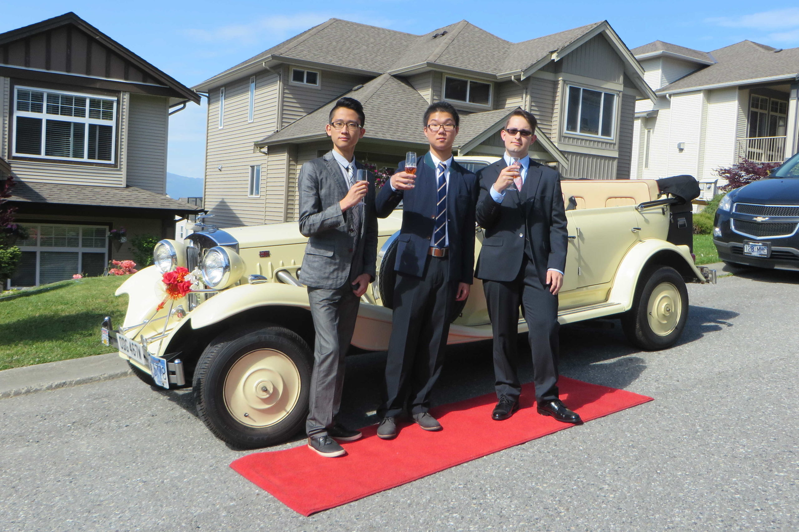 Gentlemen posing on red carpet before graduation by Vancouver Classic White Convertible Limo