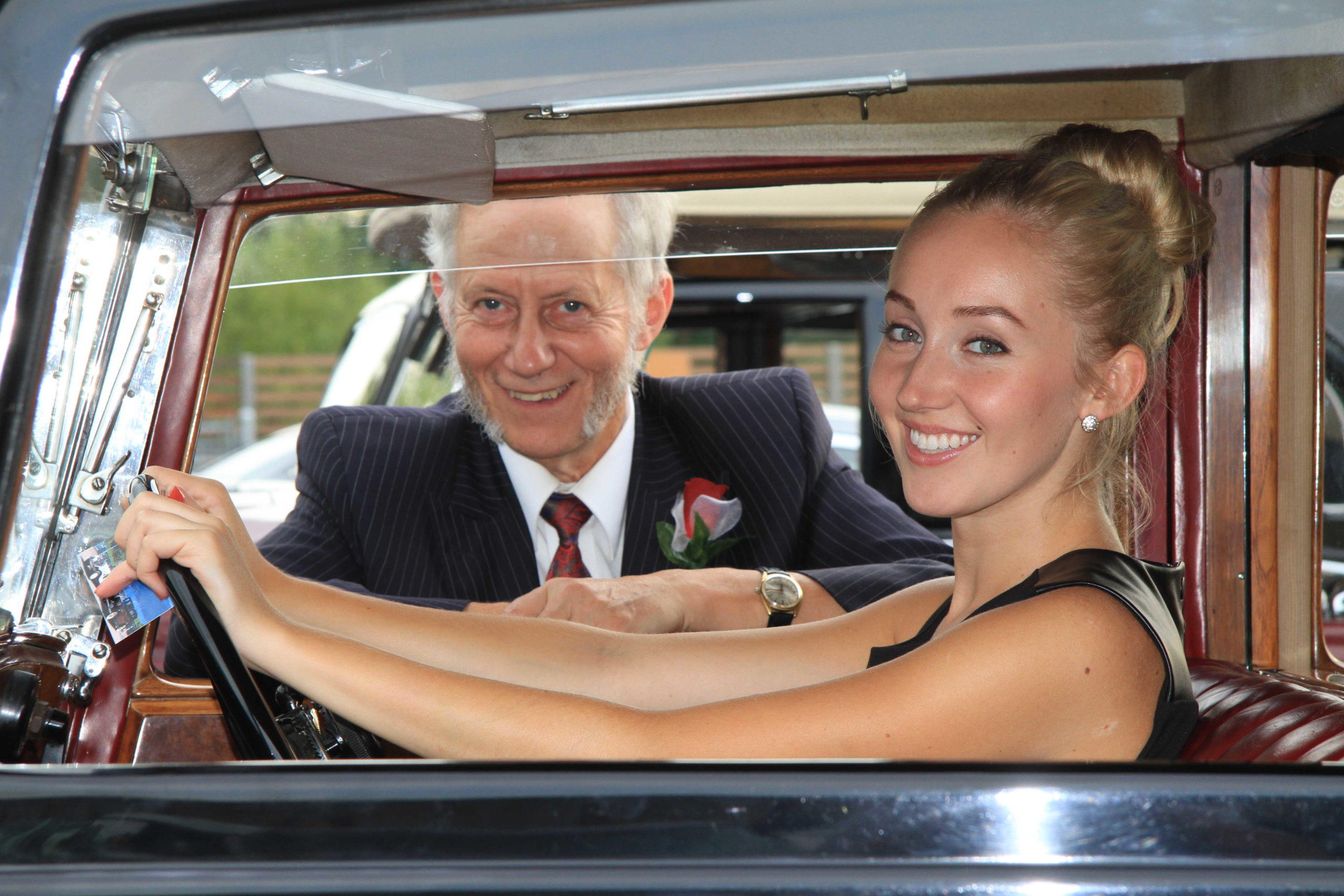 Grad poses driving classic vancouver limo
